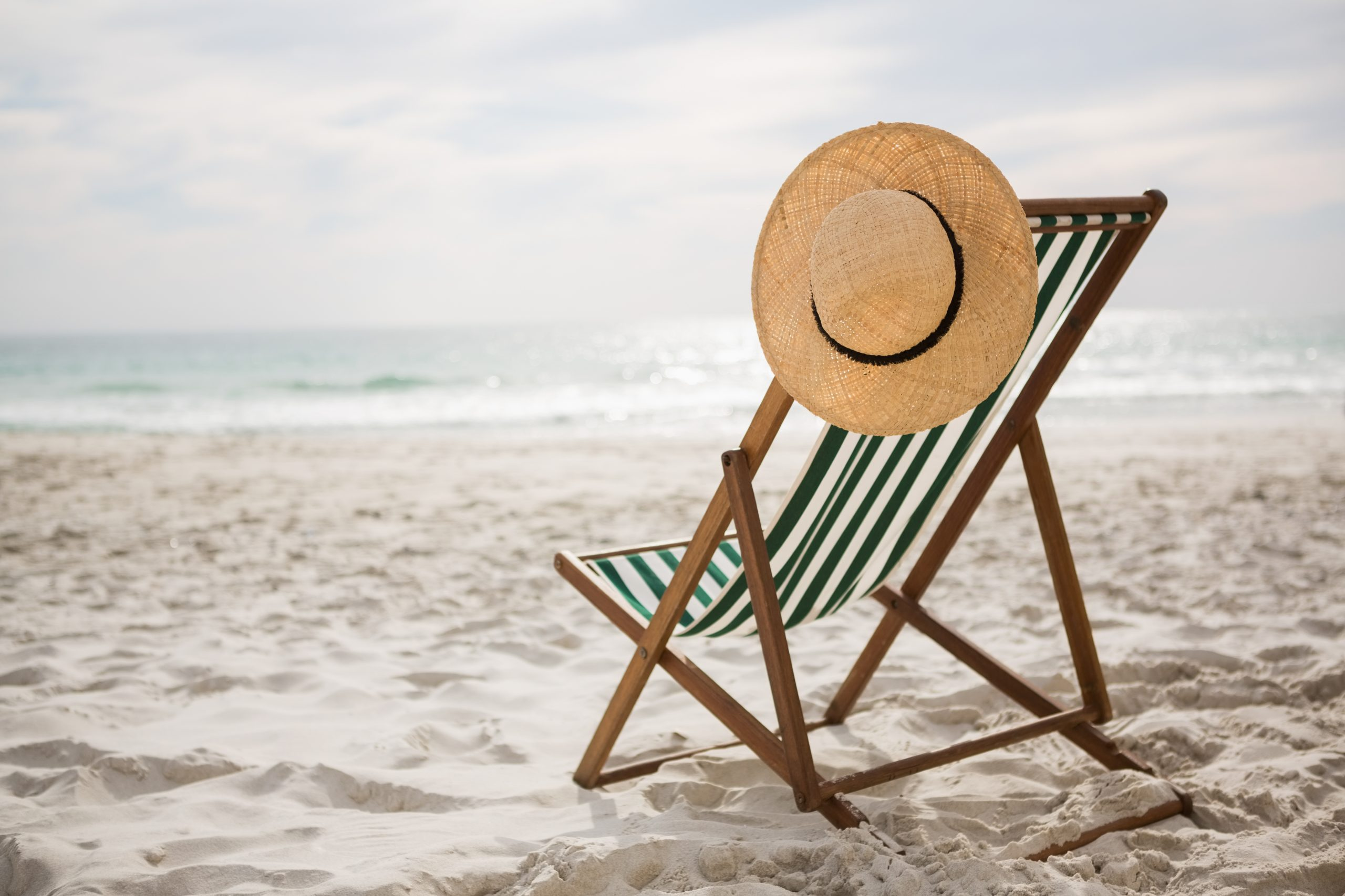 straw hat kept on empty beach chair scaled - Bonnes vacances !